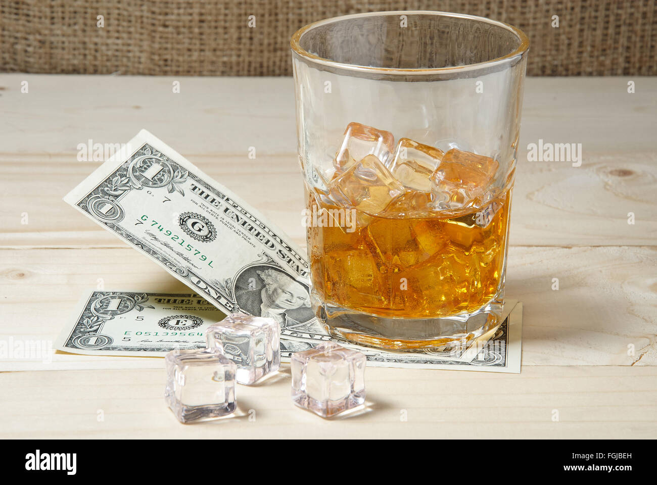 Dollars and glass of whiskey with ice on wooden table - Stock Image