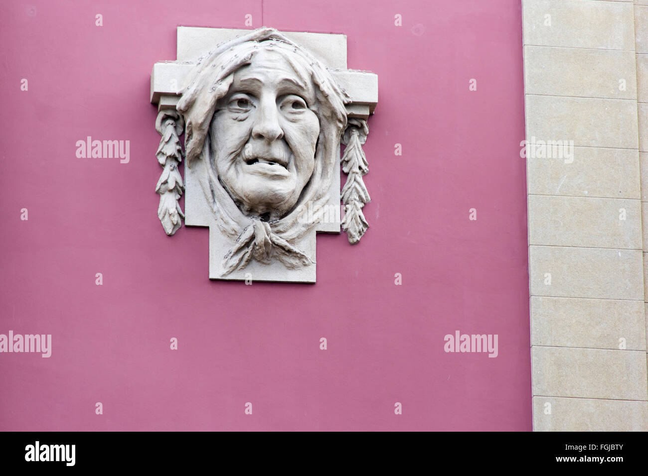 countenance, visage, phiz, mug, frontispiece, feature, muz, face, appearence, wall, sculpture, carving, sculp, pink, - Stock Image
