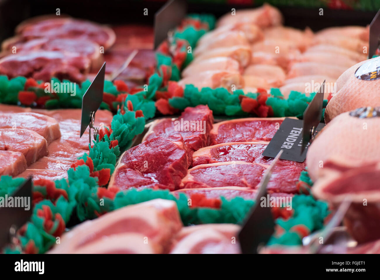Red meat on display in a butcher's shop window. - Stock Image