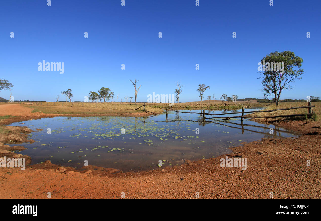 Australian outback waterhole, billabong with rustic fence, red soil and blue sky - Stock Image