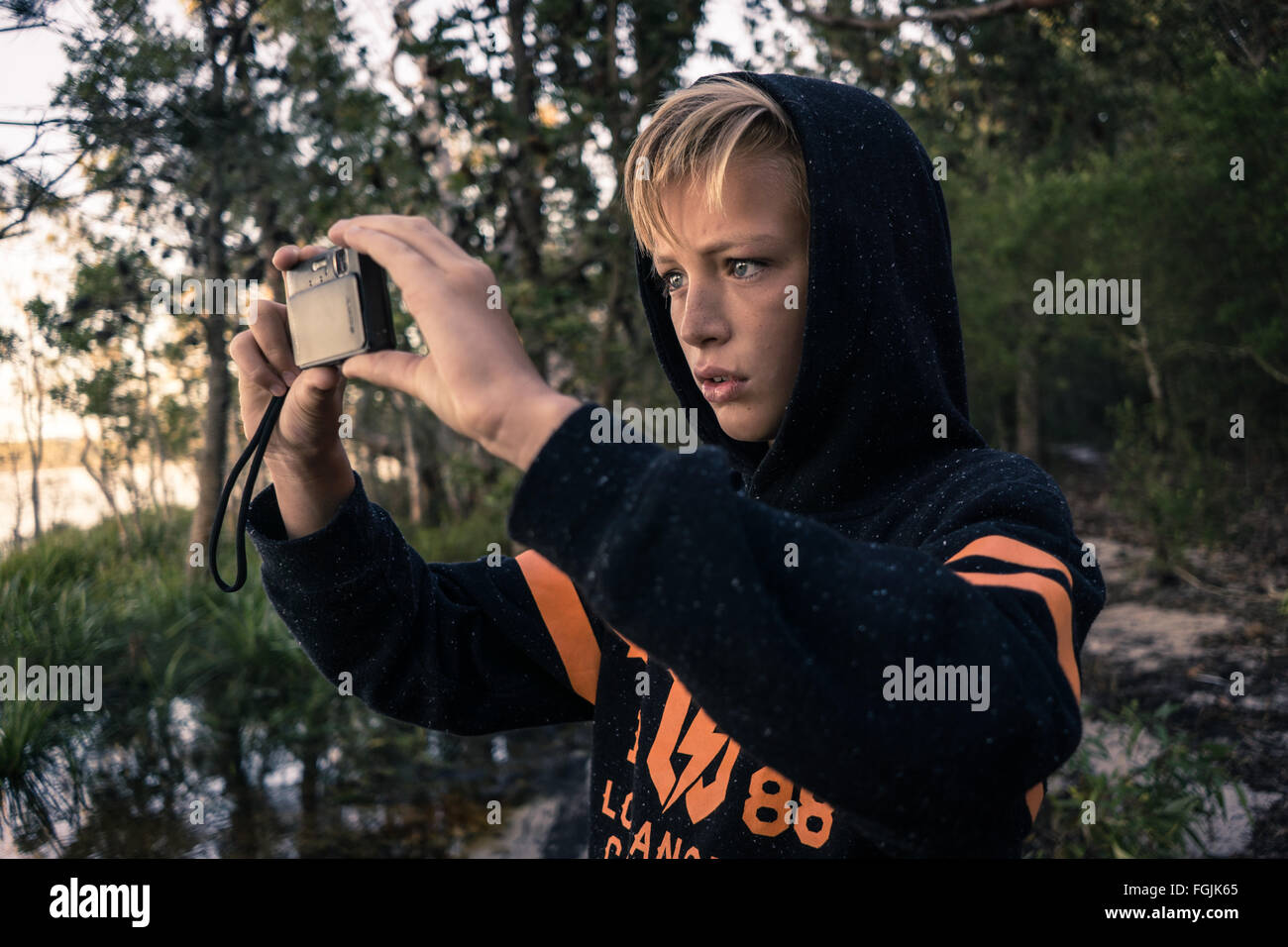 A boy taking a photo whilst on an adventure in the woods by the lake - Stock Image