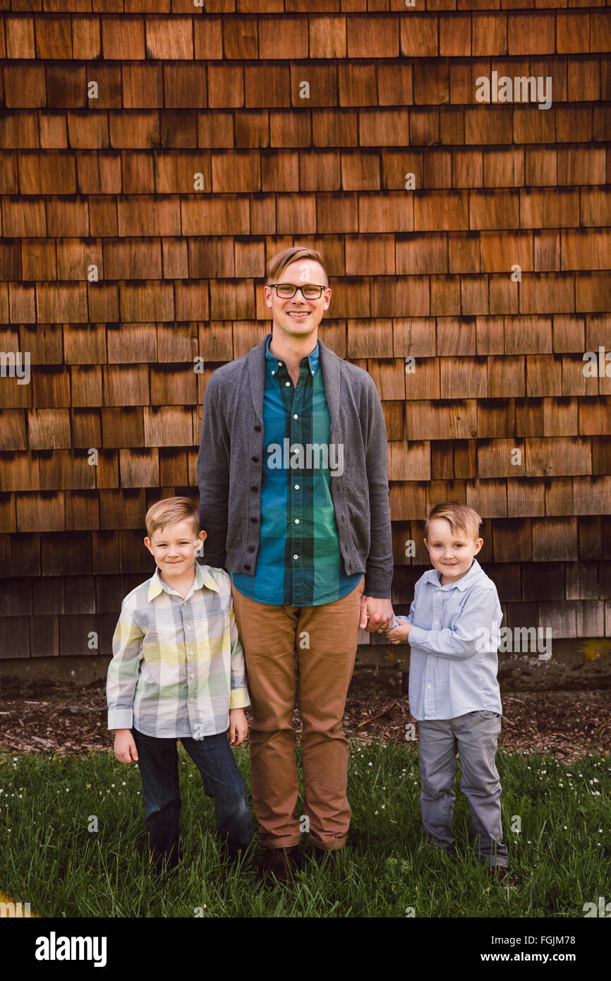 Dad with two kids, both boys, in a lifestyle portrait outdoors. - Stock Image