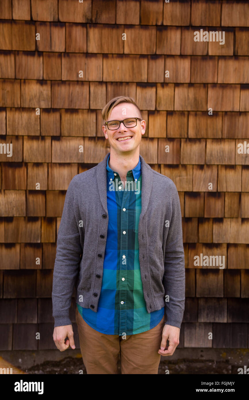 Lifestyle portrait of a man outdoors in a natural setting next to a barn. - Stock Image