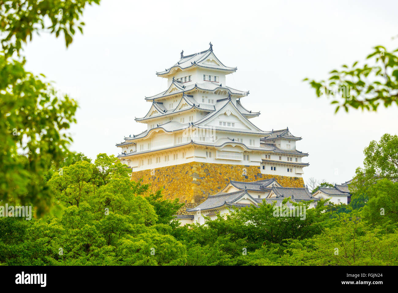 Trees and leaves framing the beautiful details of Himeji-jo castle on overcast day in Himeji, Japan after 2015 renovations - Stock Image