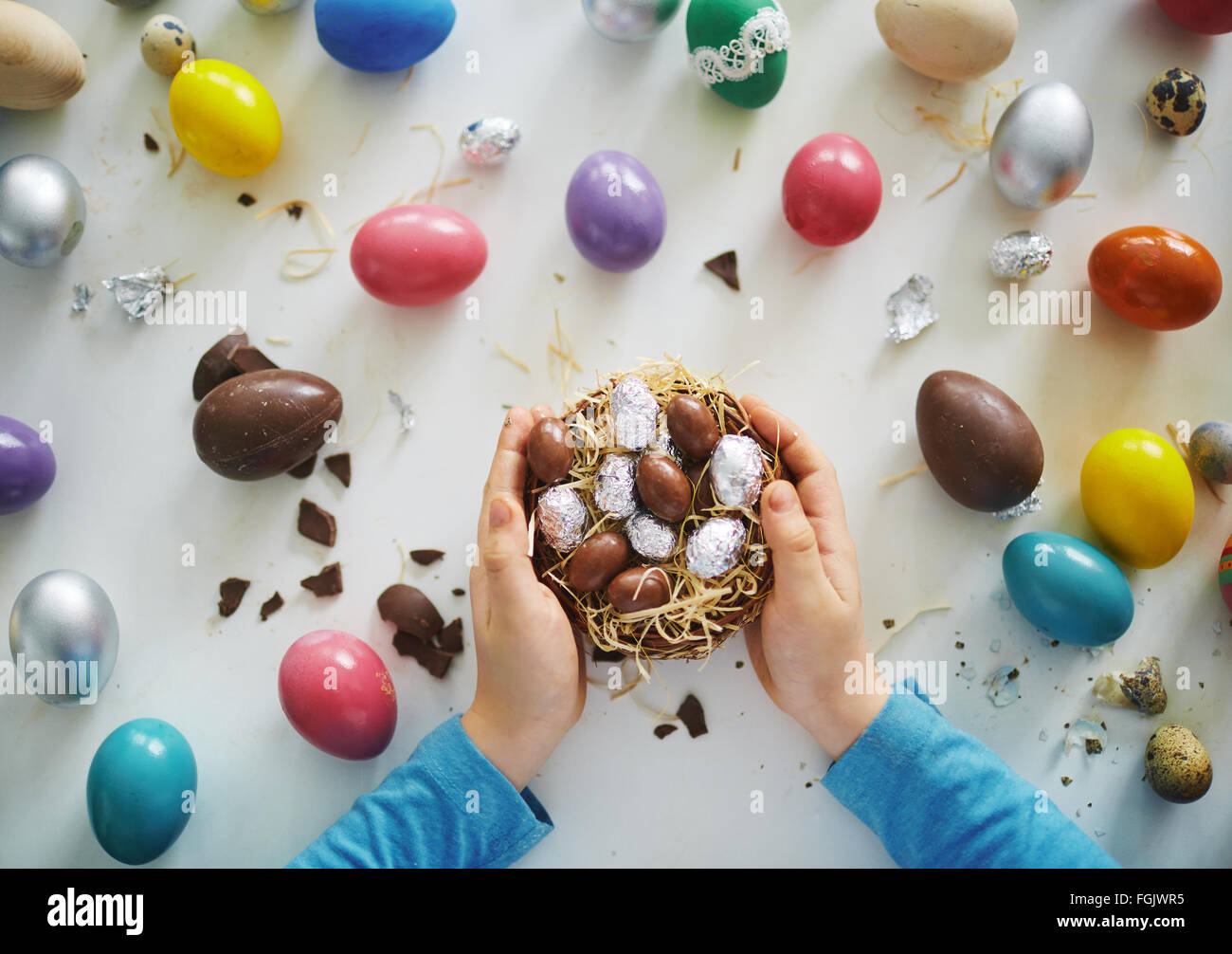 Hands of child holding small nest with chocolate eggs - Stock Image