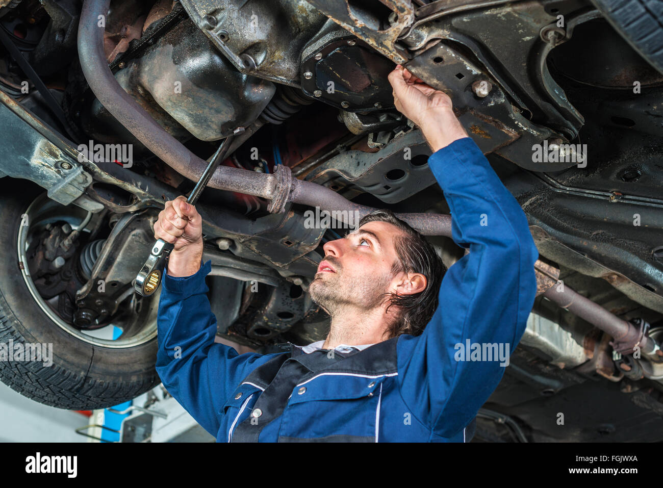 Mechanic checking the condition of a lifted car - Stock Image