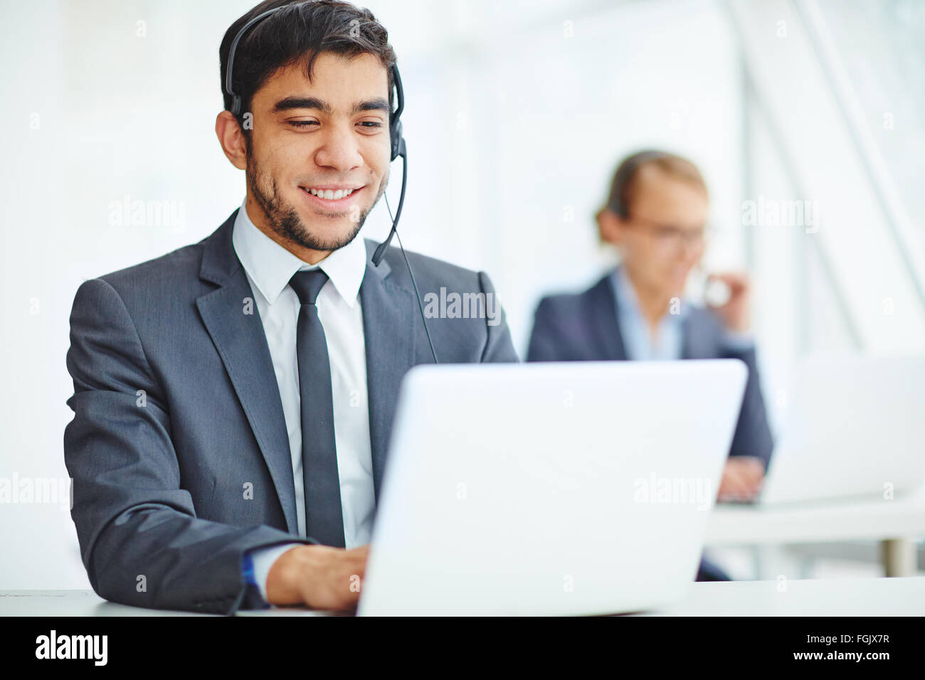 Young manager with headset typing during online consultation - Stock Image