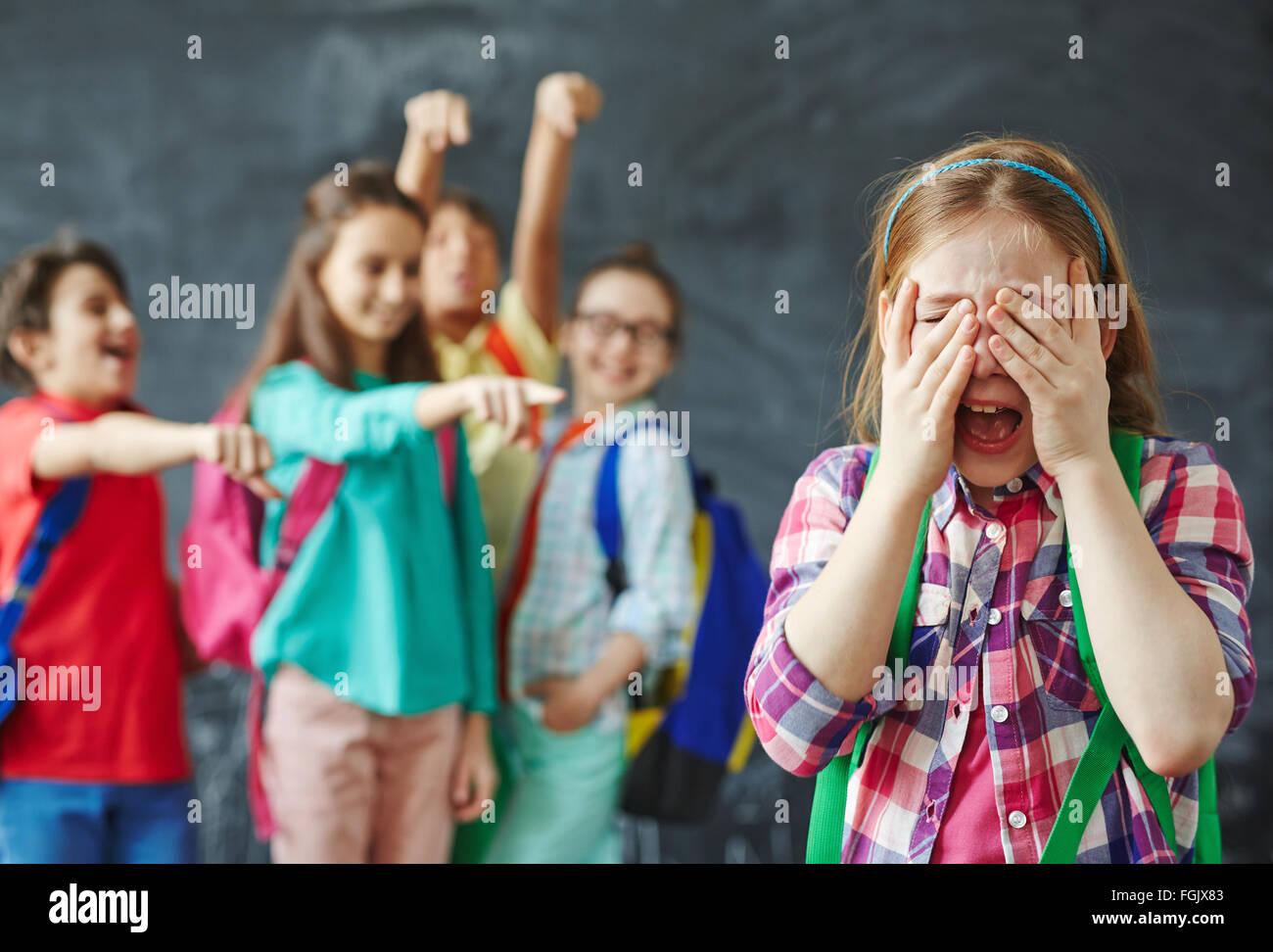 Schoolgirl crying on background of teasing classmates - Stock Image