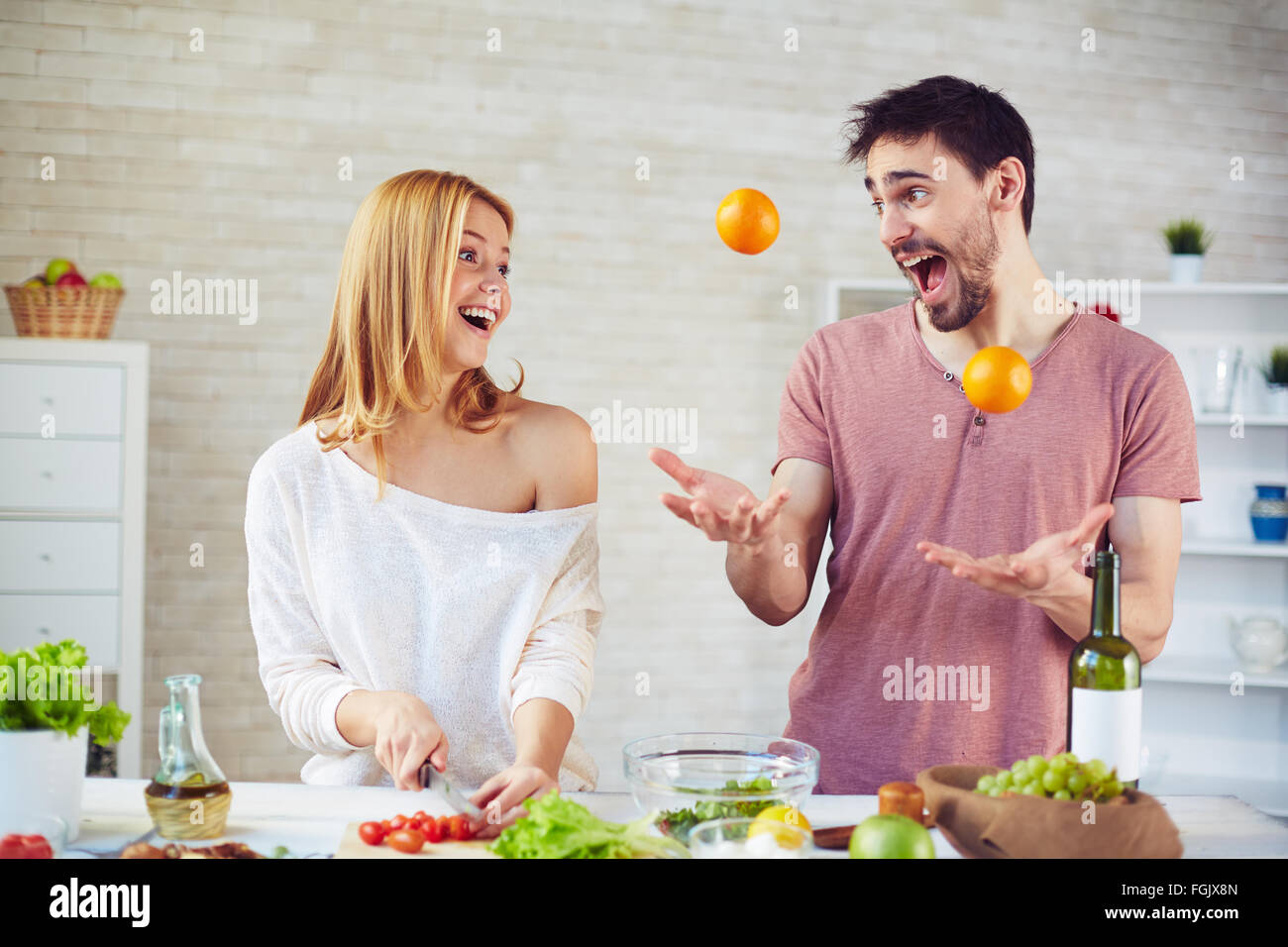 Playful young man juggling citrus fruits with his amazed wife cooking near by - Stock Image