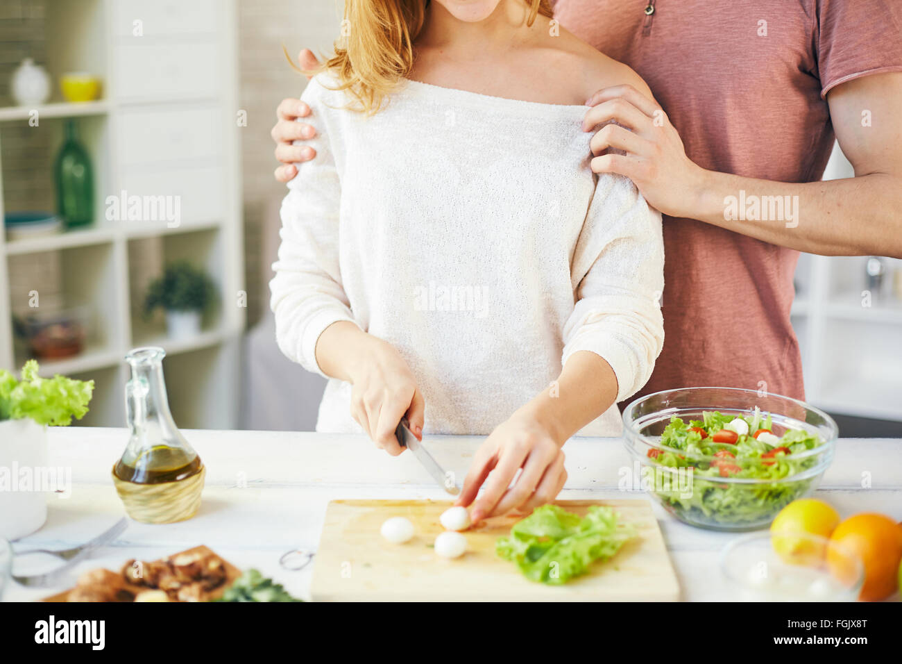 Young housewife cutting cheese for salad while her husband embracing her - Stock Image