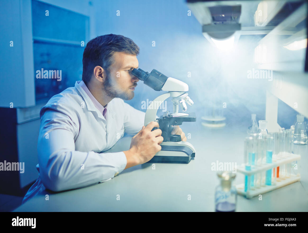 Contemporary scientist with microscope carrying out microbiological investigation - Stock Image