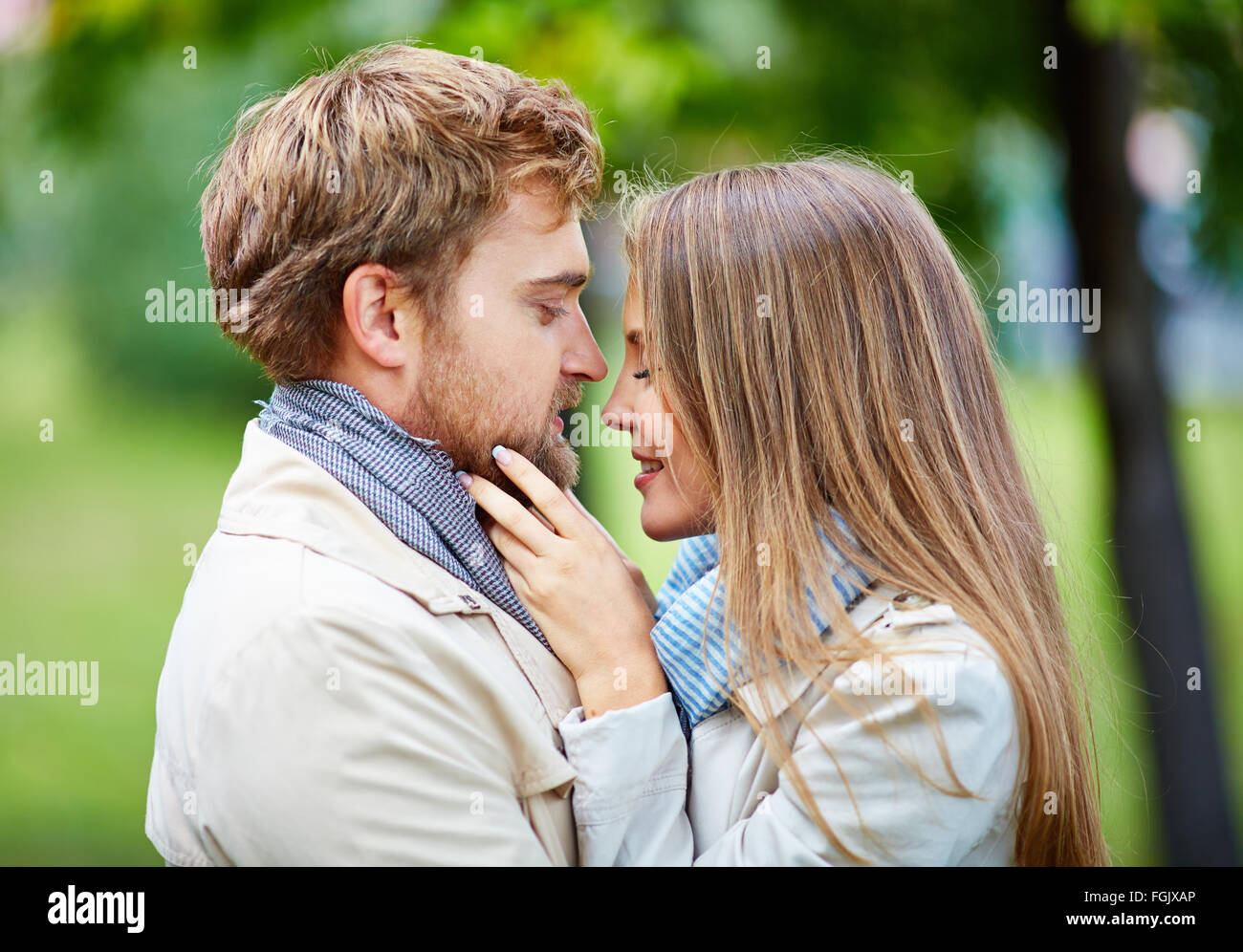 Happy young couple flirting in park - Stock Image