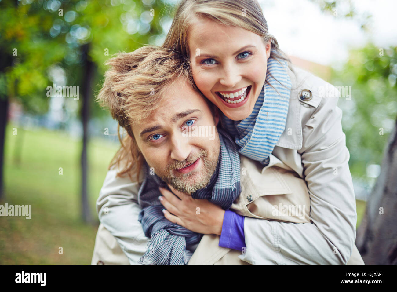 Ecstatic couple looking at camera outdoors - Stock Image
