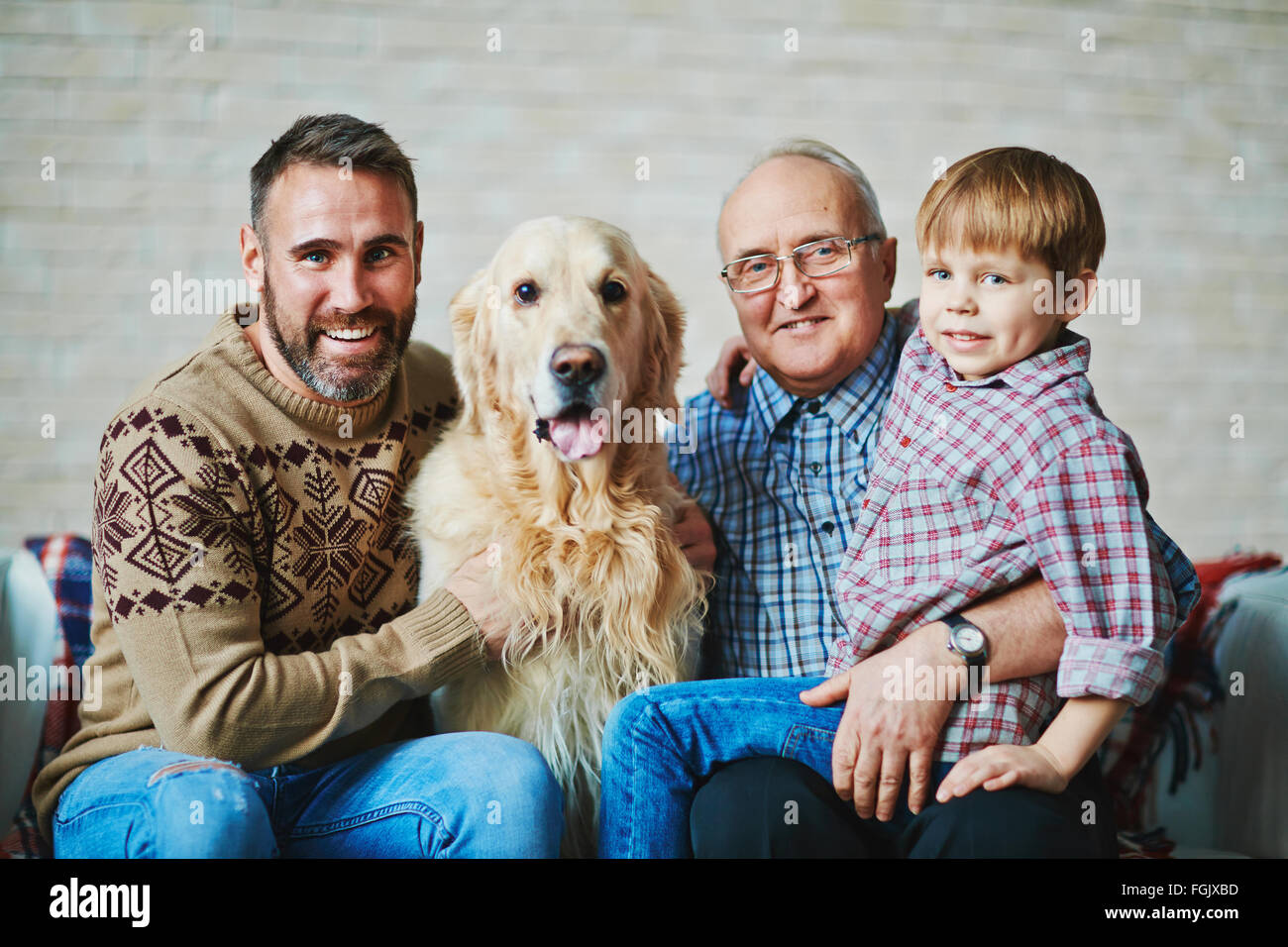 Mature man, young man, youngster and their pet looking at camera - Stock Image