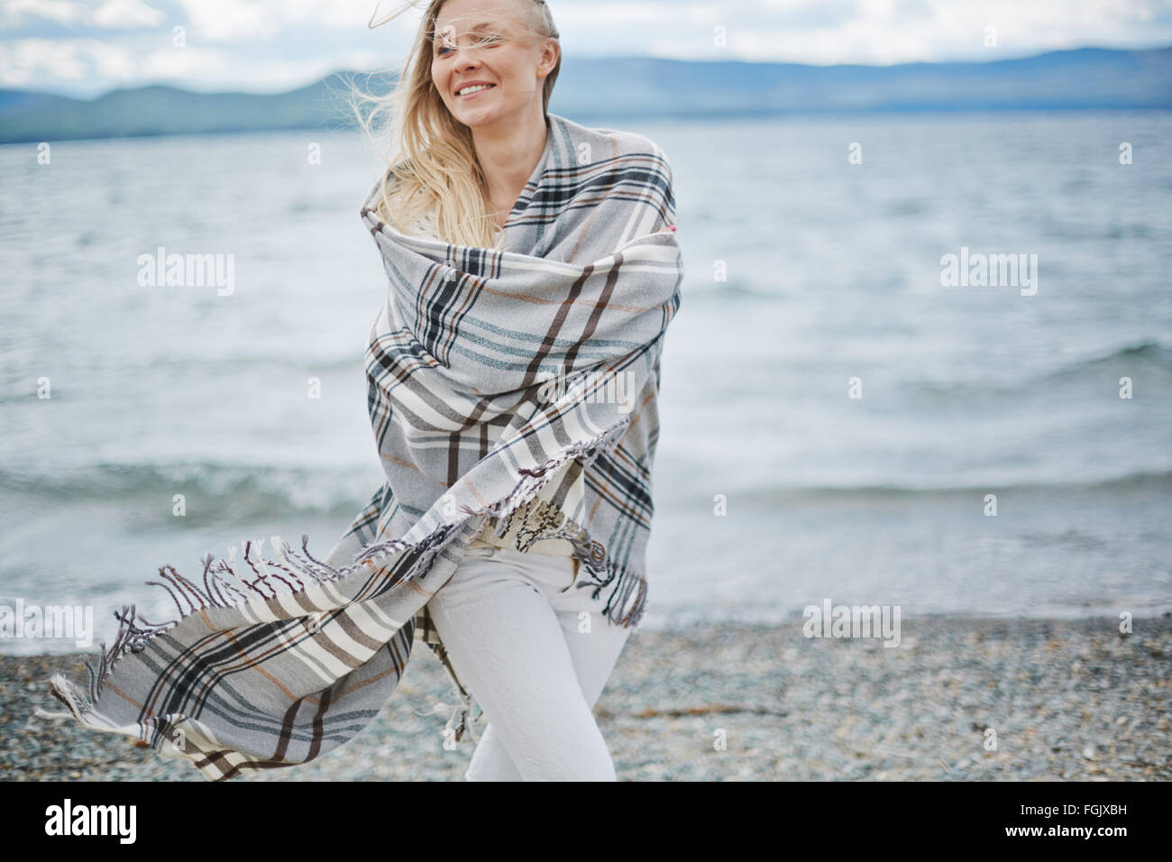 Young woman wrapped in plaid walking on the beach - Stock Image