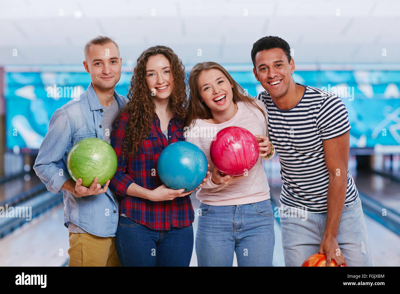 Friendly guys and girls holding bowling balls - Stock Image
