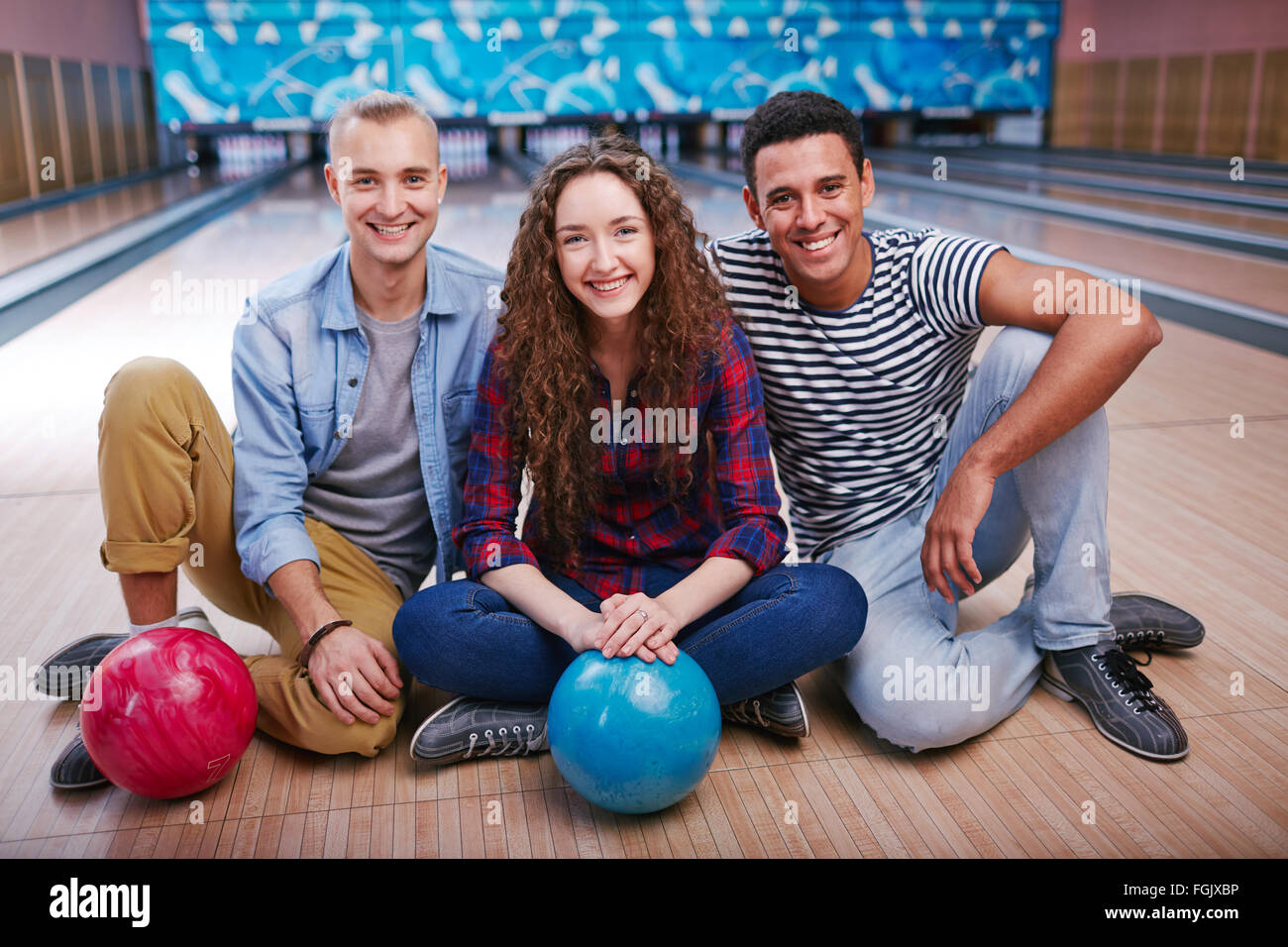 Friendly people with bowling balls sitting on the floor at bowling alley - Stock Image