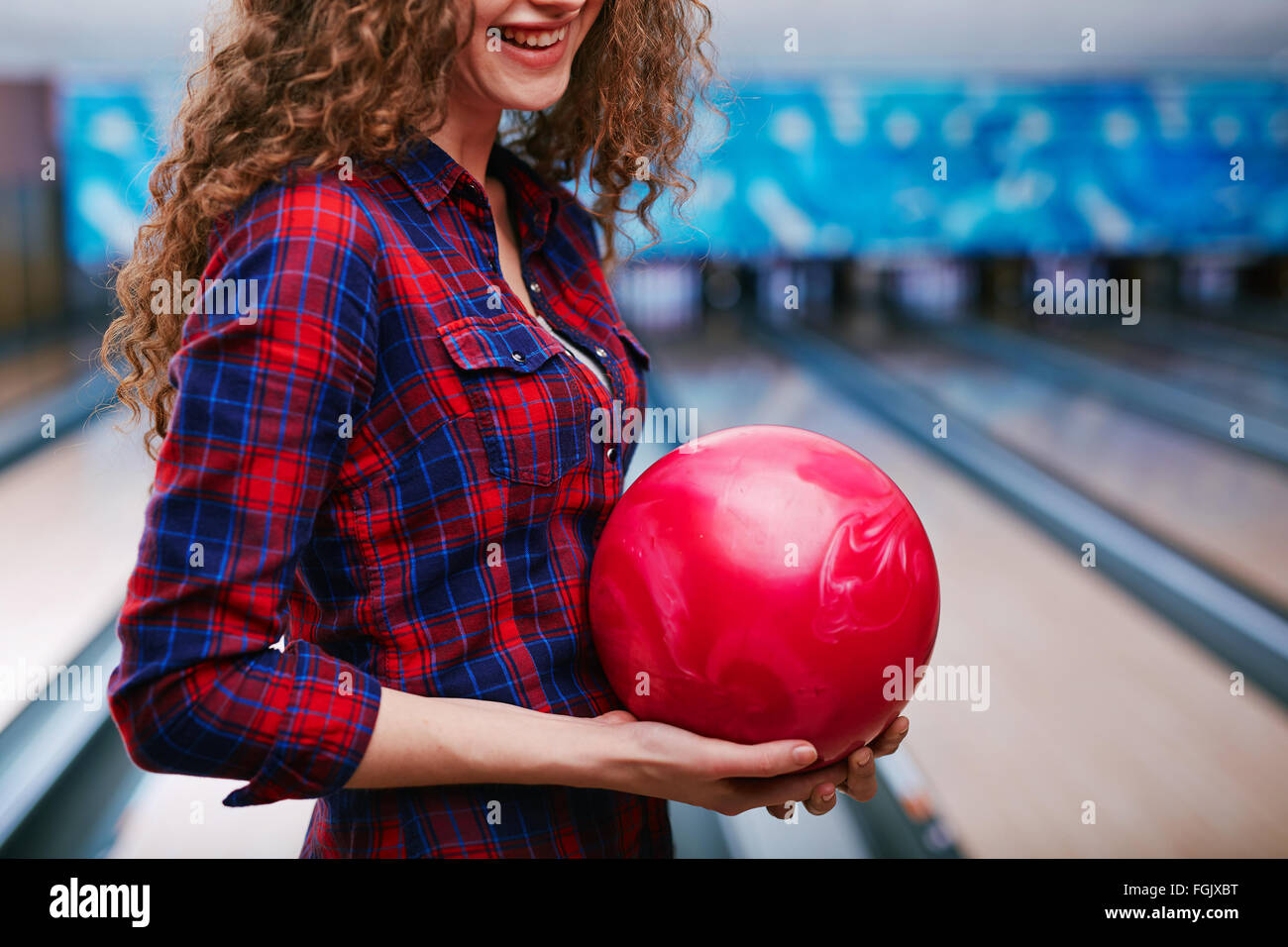 Happy girl holding bowling ball - Stock Image