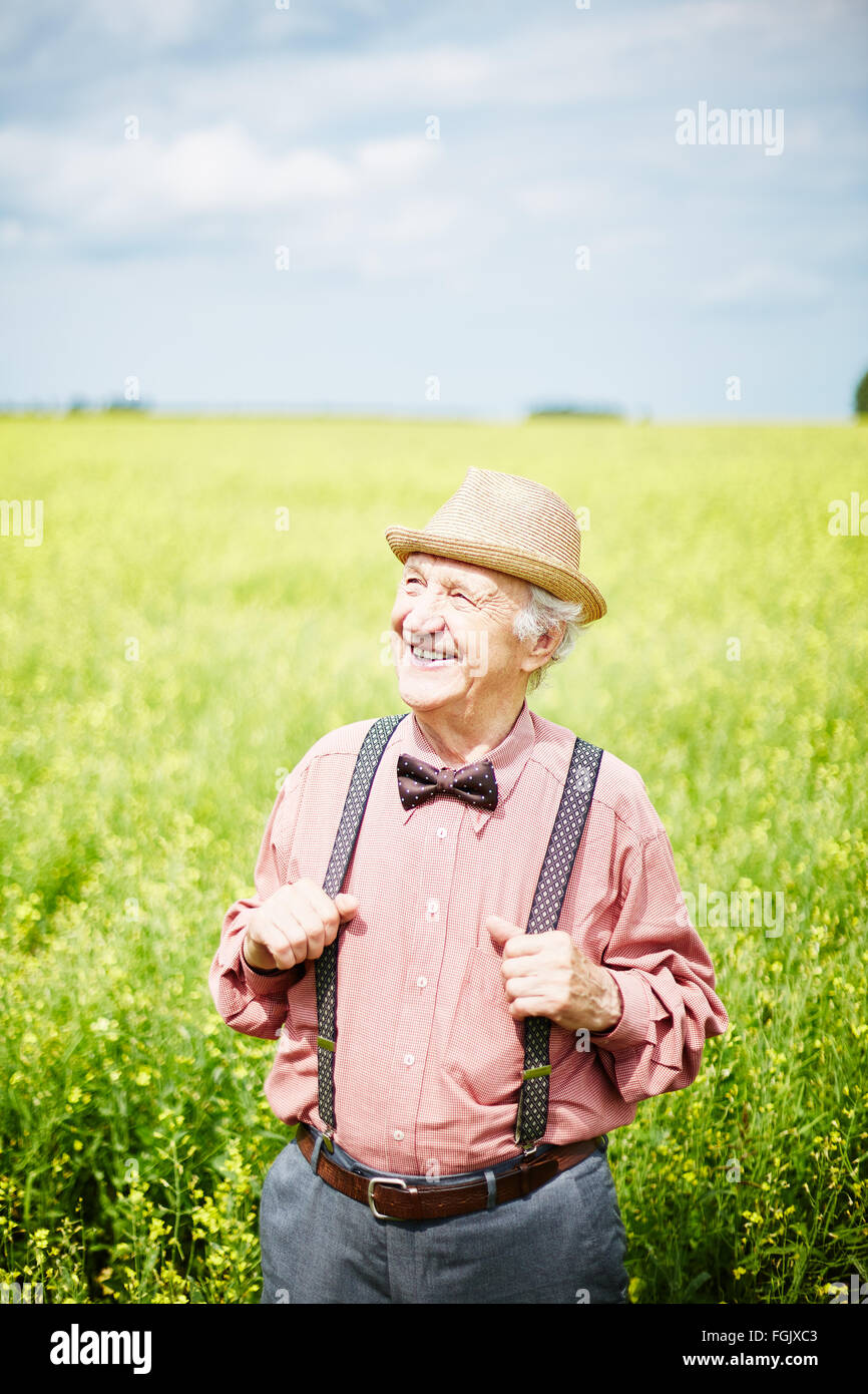 Well-dressed senior man standing in meadow on sunny day - Stock Image