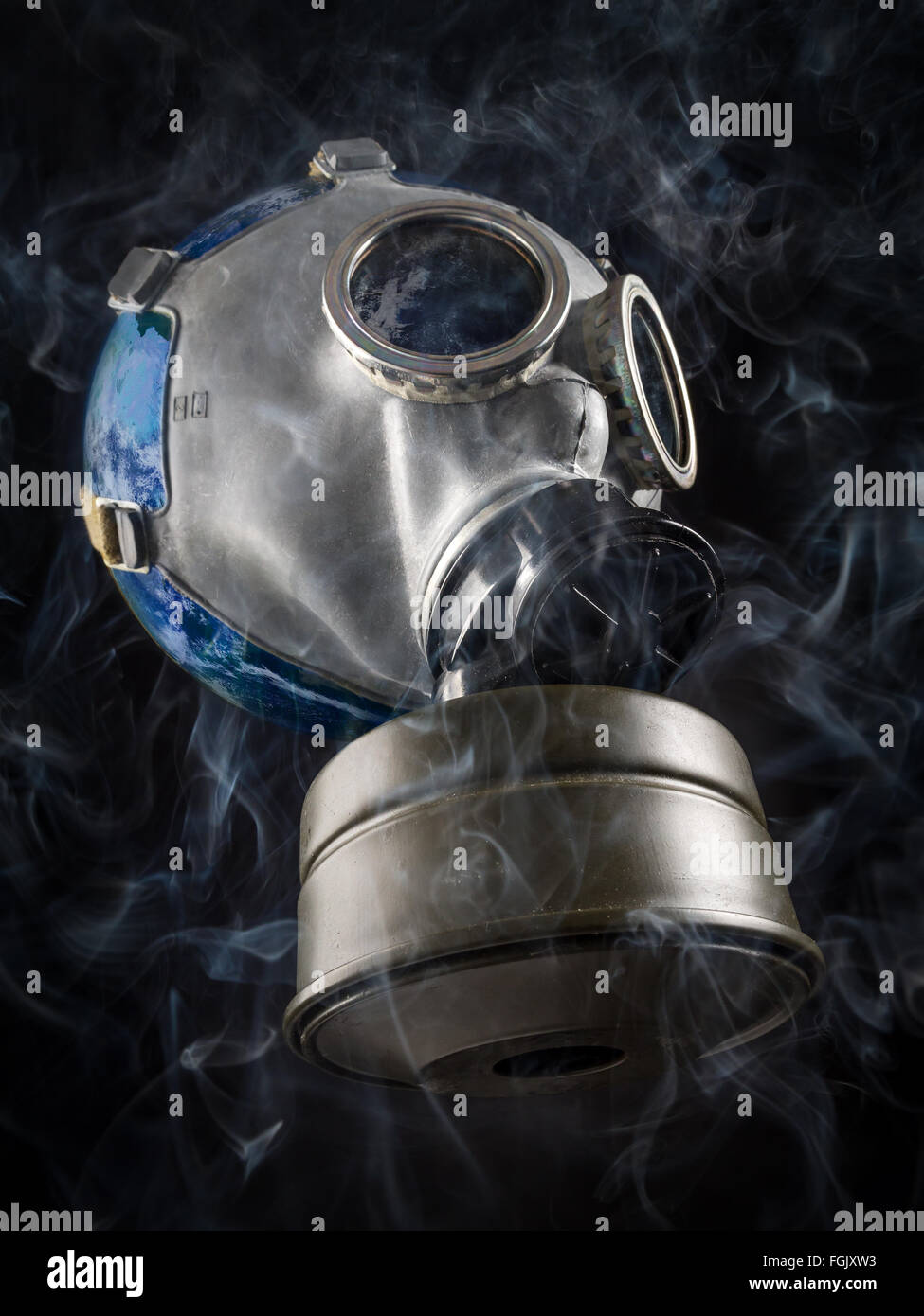 Planet Earth with gas mask as a metaphor of global air pollution - Stock Image