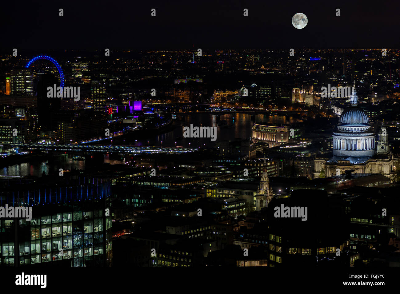 The full moon rising over the city of London England - Stock Image