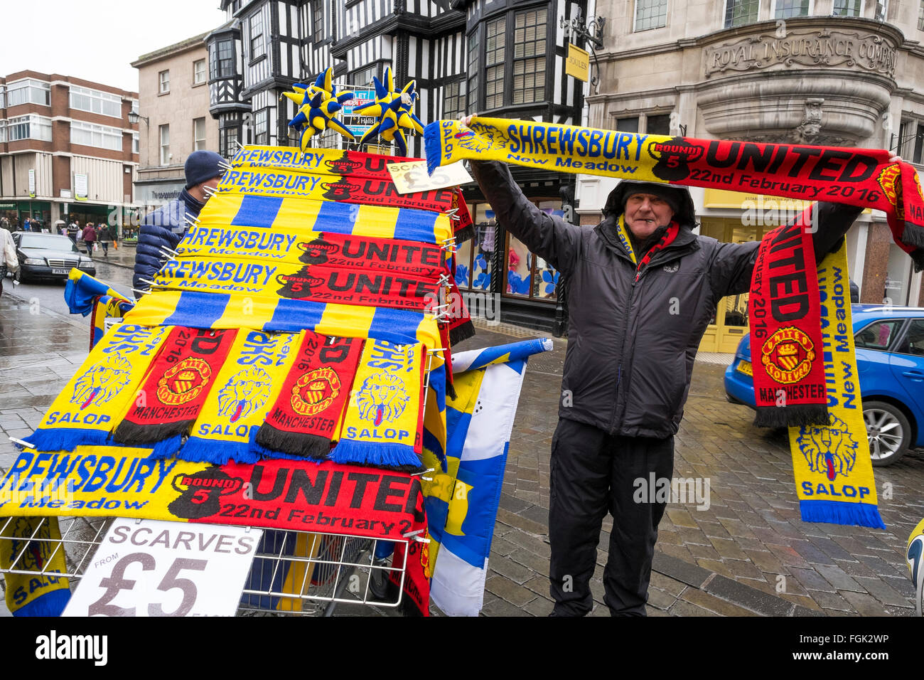 Shrewsbury, UK. Saturday 20 February 2016. Stallholder selling scarves in medieval Shrewsbury town centre, ahead - Stock Image