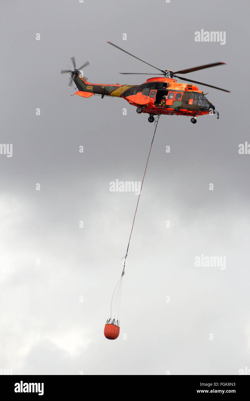 Spanish Air Force Eurocopter Cougar helicopter with a water bucket for firefighting - Stock Image
