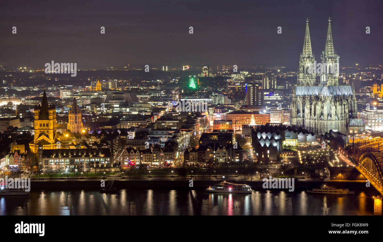 Night view of the Cologne Cathedral and railway bridge over the Rhine river, Germany - Stock Image