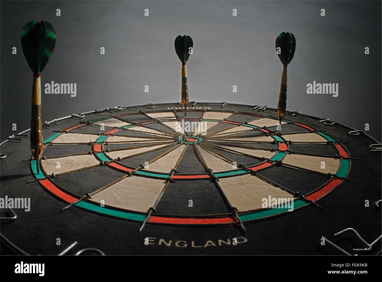 Three old-fashioned darts with feather flights in a dartboard, looking from below - Stock Image