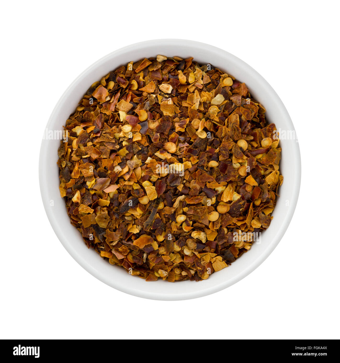 Crushed Red Pepper in a Ceramic Bowl. The image is a cut out, isolated on a white background. - Stock Image