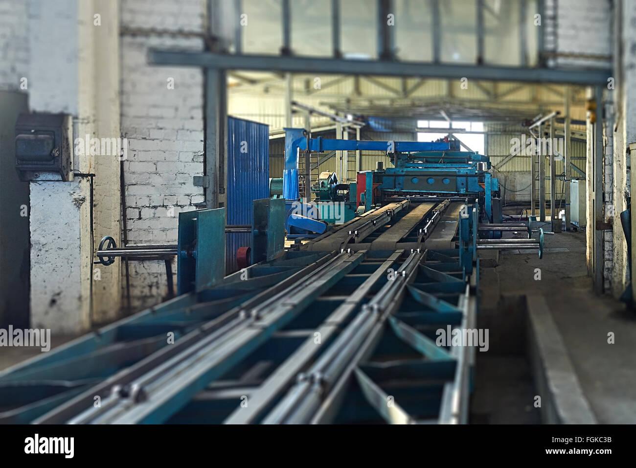 machine for slitting steel sheet. Tilt-shift effect. - Stock Image