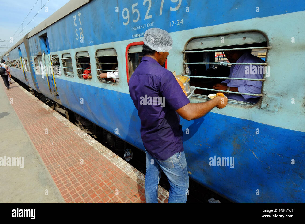 A food vendor selling food through the carriage window at a station in Southern India - Stock Image
