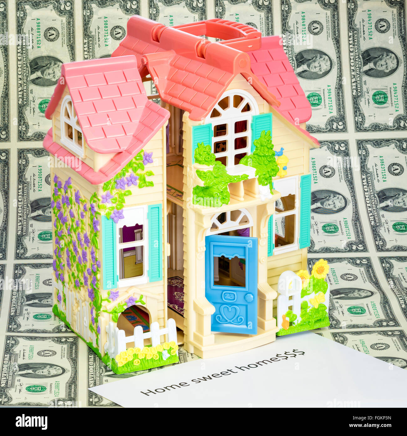 Cute little doll house on money with Home Sweet Home sign - Stock Image
