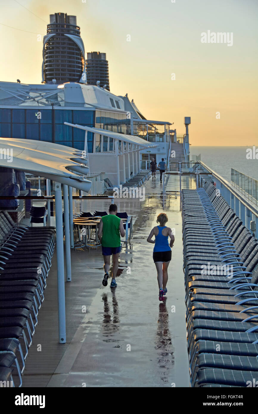 Cruise ship liner deck early morning joggers running with care along dedicated  circuit between sun loungers after - Stock Image