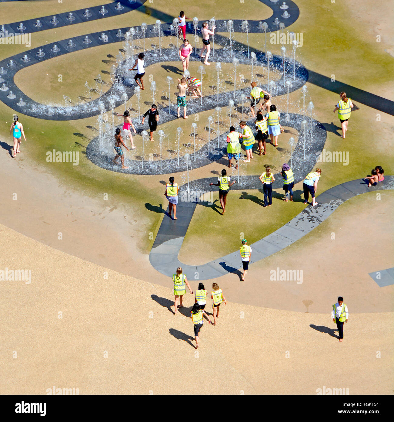 Kids playing outdoors in water fountain jets on school trip on hot summer day in Queen Elizabeth Olympic Park London - Stock Image
