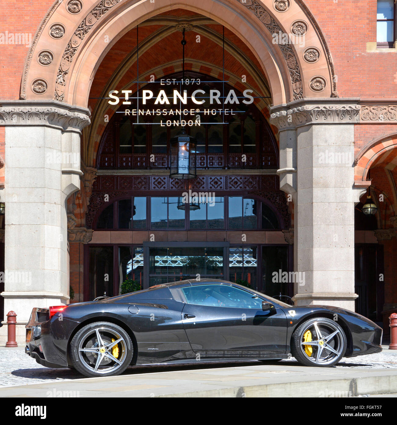 Ferrari luxury Italian sports car parked outside St Pancras Renaissance Hotel located  front of St Pancras Eurostar - Stock Image