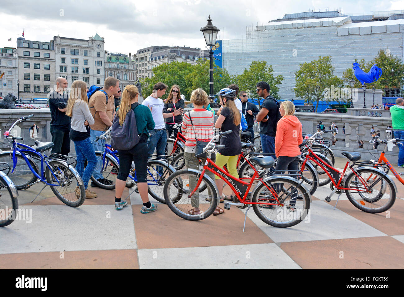 Tour guide leader talking to a group of sightseeing tourists cycling around London seen here during a stop in Trafalgar - Stock Image