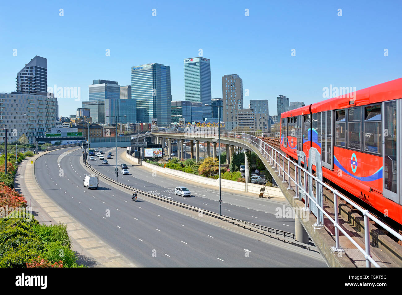 Canary Wharf skyline DLR train leaves East India station in London Docklands & crosses Aspen Way dual carriageway - Stock Image