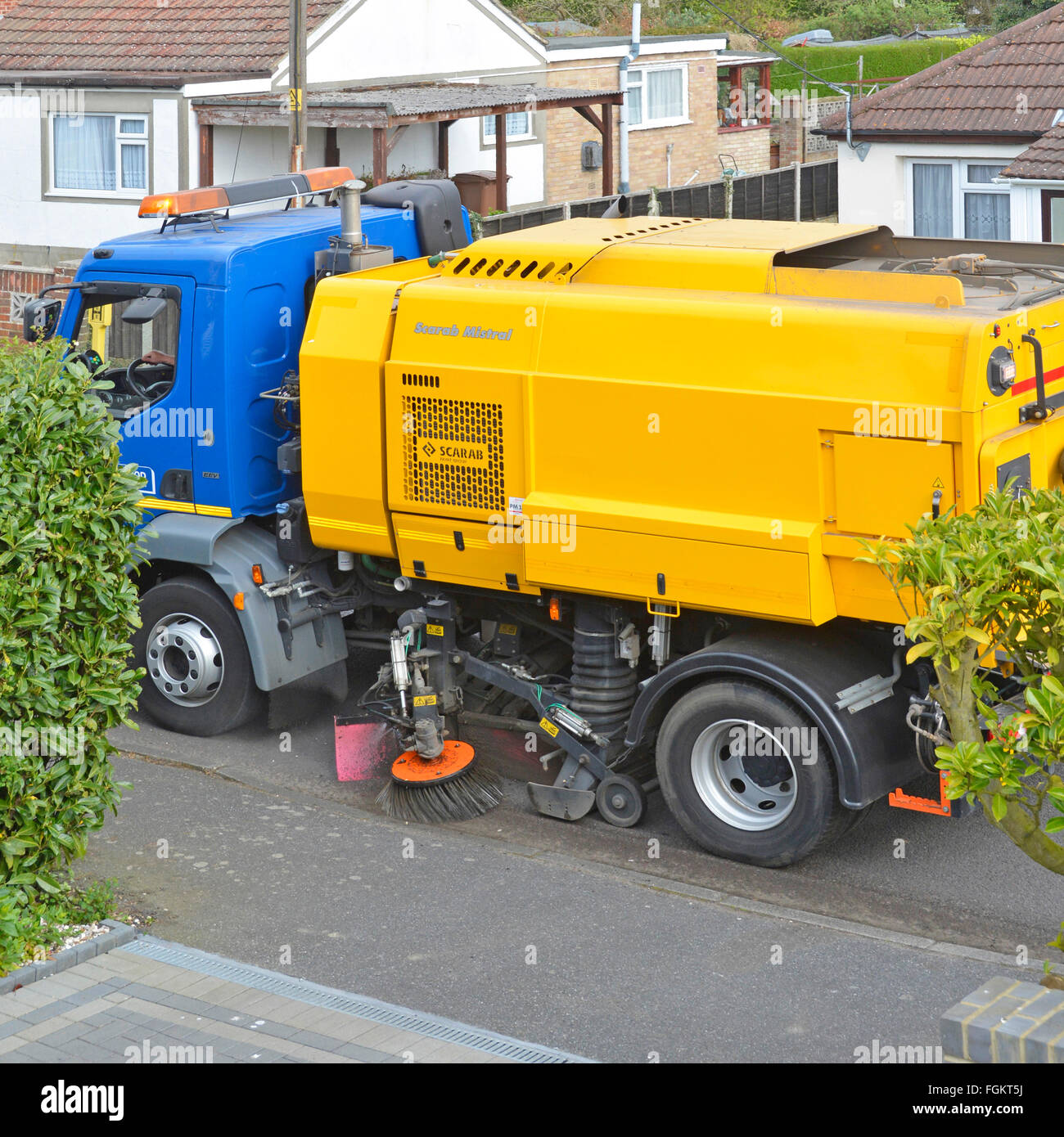 Local government gutter cleaning services via mechanical sweeper brushes mounted on Daf lorry passing domestic property - Stock Image
