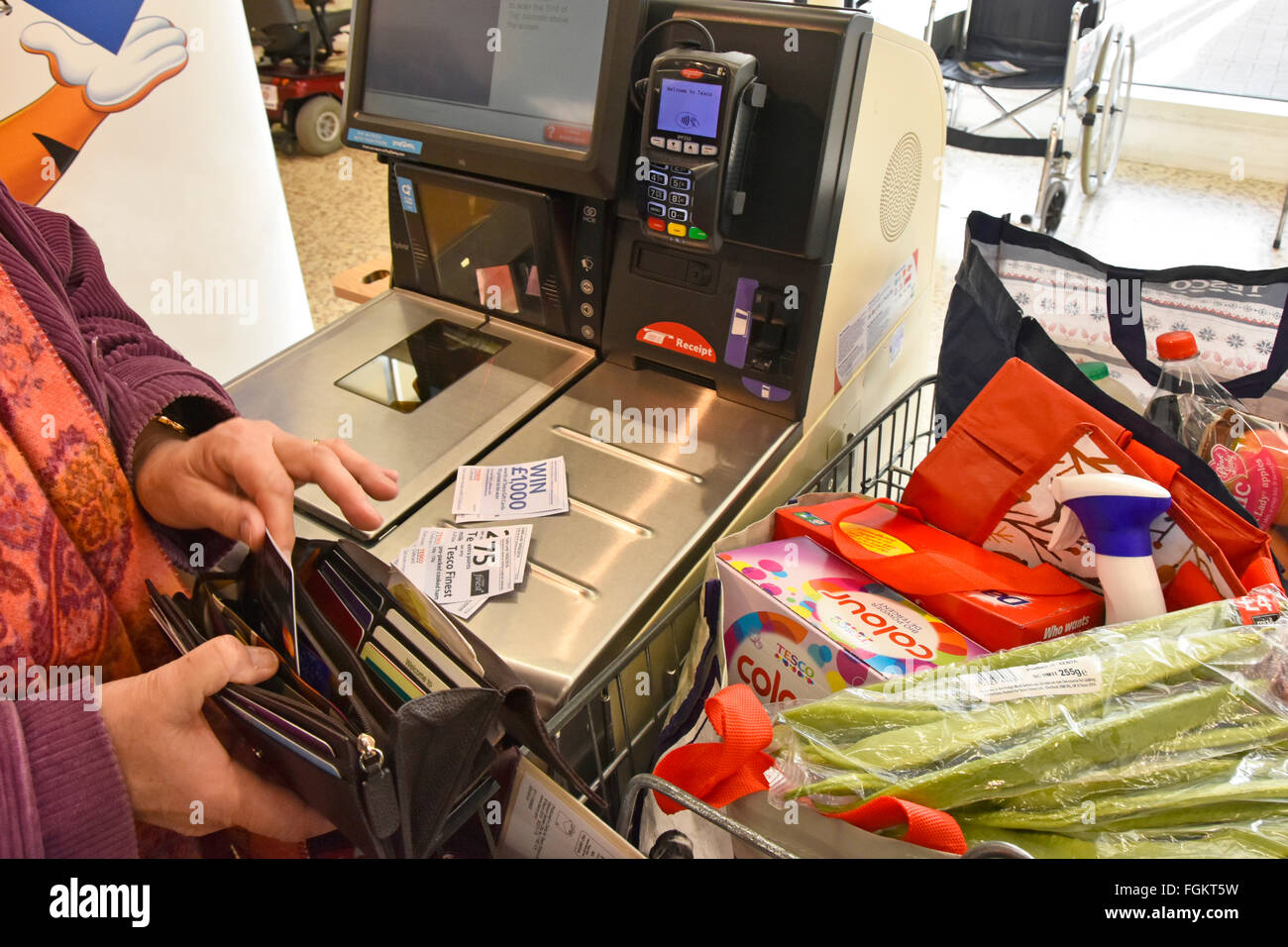 Supermarket checkout shopper removes her coupons & credit card from purse at self service checkout to pay for - Stock Image