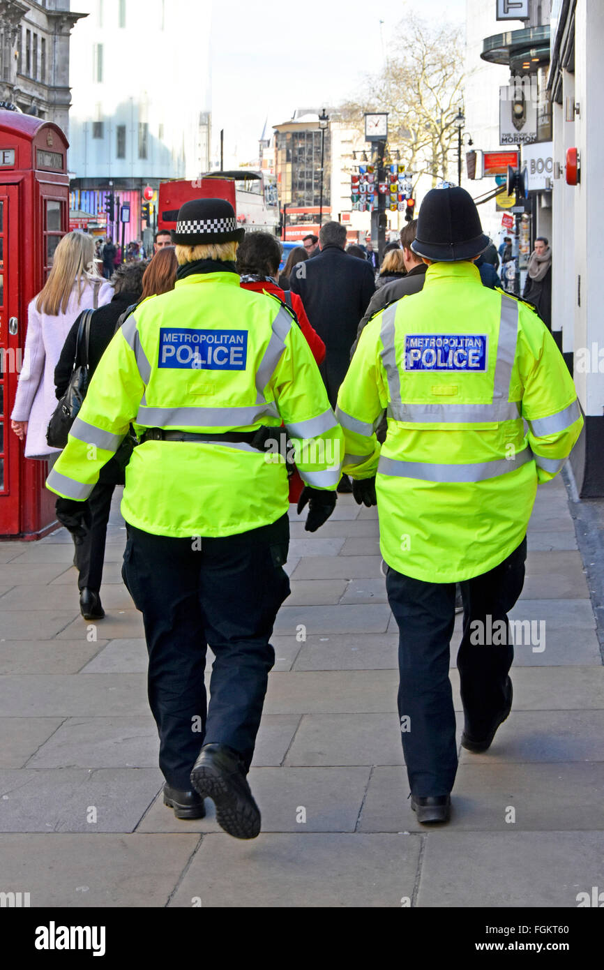 Metropolitan Police back view female officer in distinctive cap left & male officer traditional helmet patrolling - Stock Image