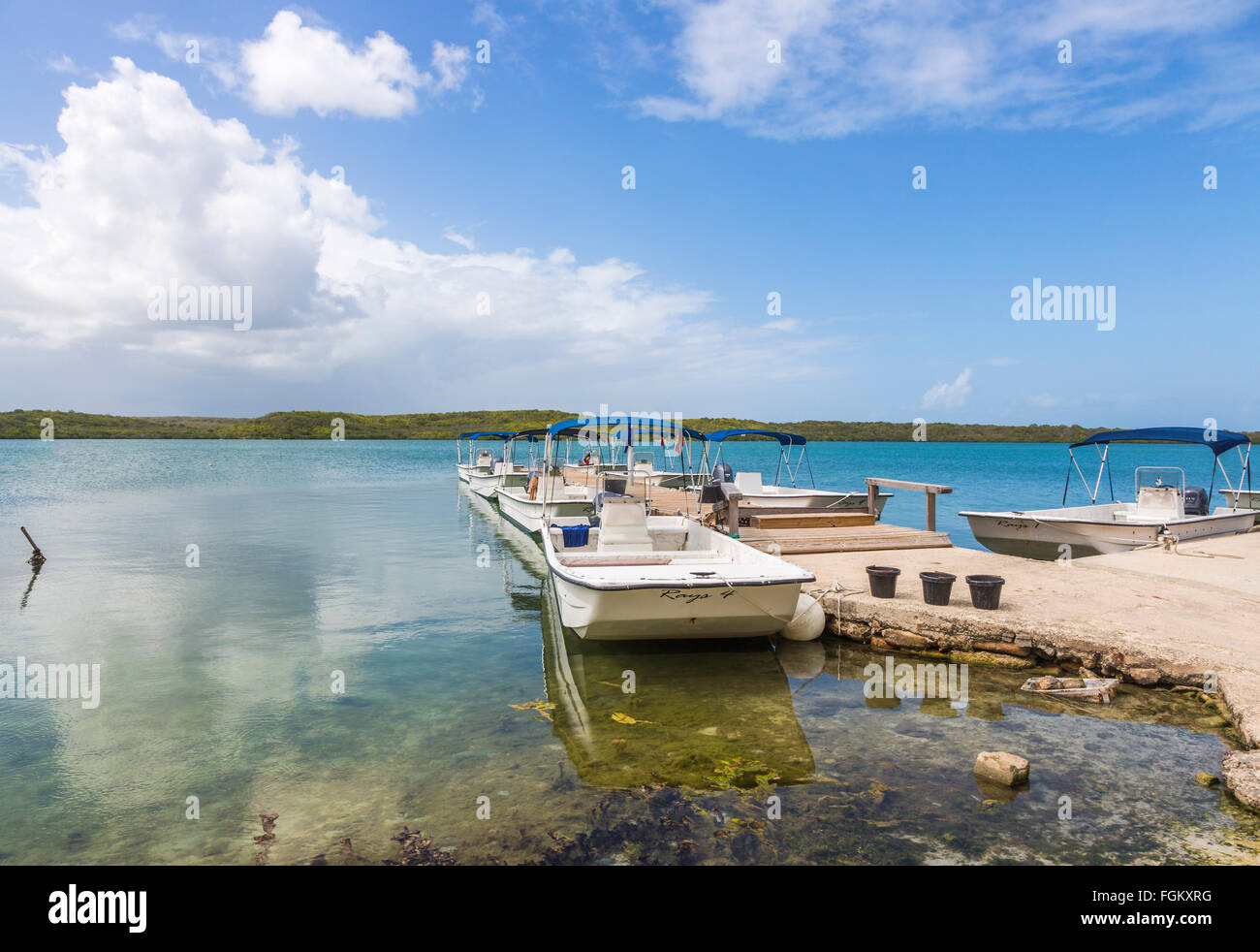 Boats moored at a jetty at Stingray City on the east coast of Antigua, Antigua and Barbuda, West Indies, blue sky, - Stock Image