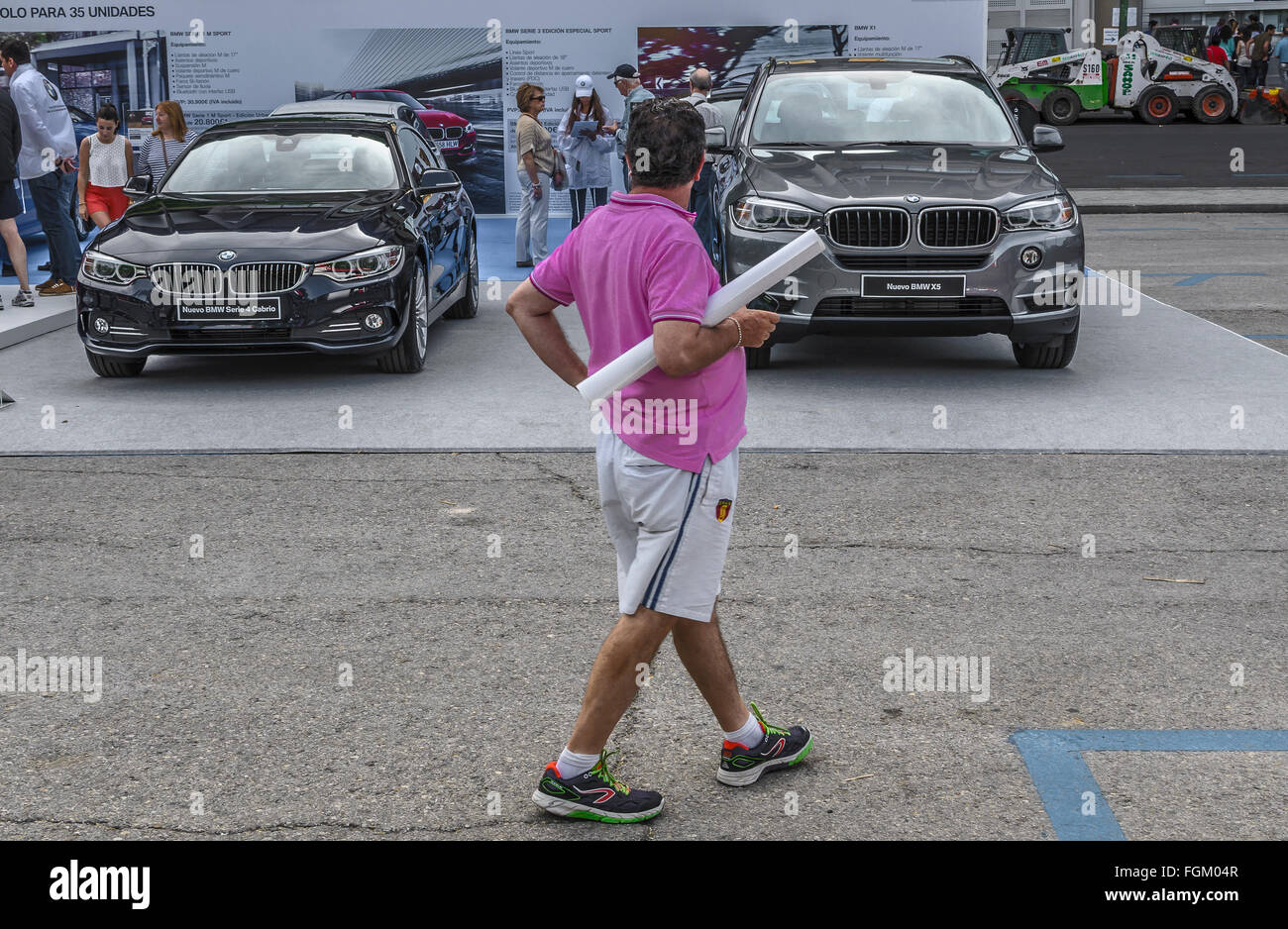 View of a man with a pink shirt in a car exhibition, Madrid city, Spain Stock Photo
