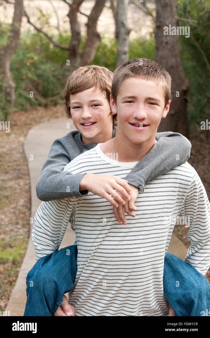 Two cute boys that are brothers riding piggy back on sidewalk smiling at camera. - Stock Image