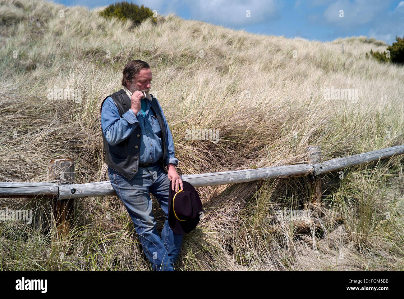 Man smoking his cigaret at the trailhead. Addiction to cigarets are too strong, the worst adiction there is on earth. - Stock Image