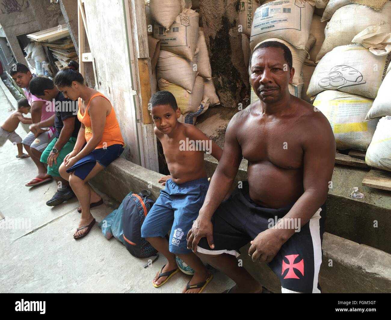 An inhabitant of the Pavao-Pavaozinho slum who calls himself 'Rocky Balboa' sitting by one of the area's - Stock Image