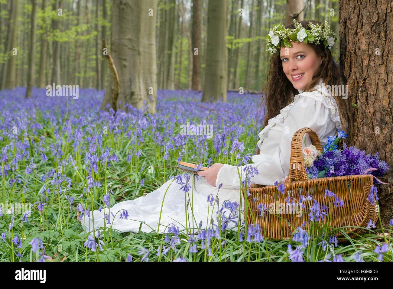 Victorian woman in white dress in a springtime bluebells forest - Stock Image