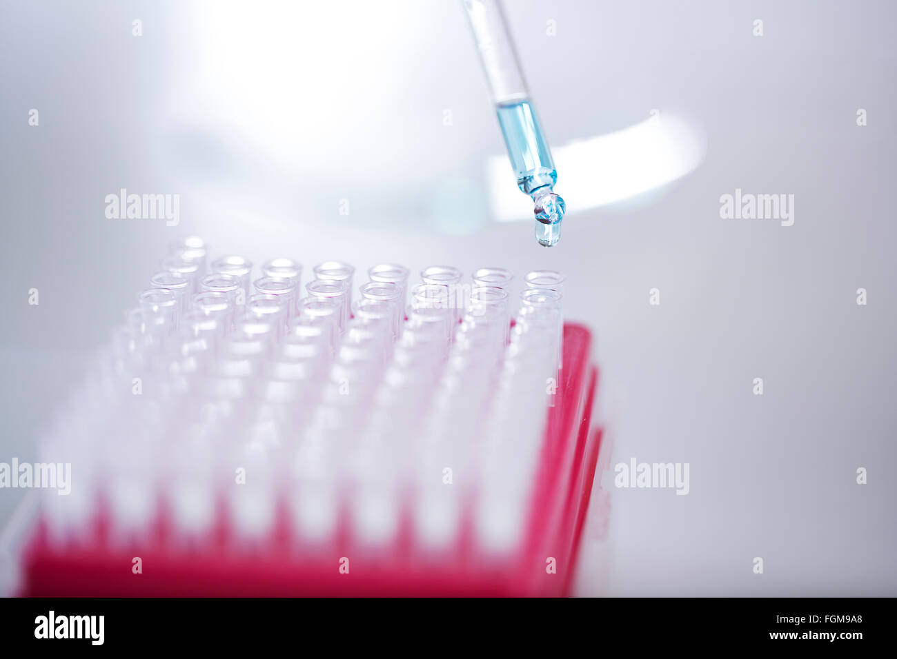Blue liquid dripping from pipette into test tube - Stock Image