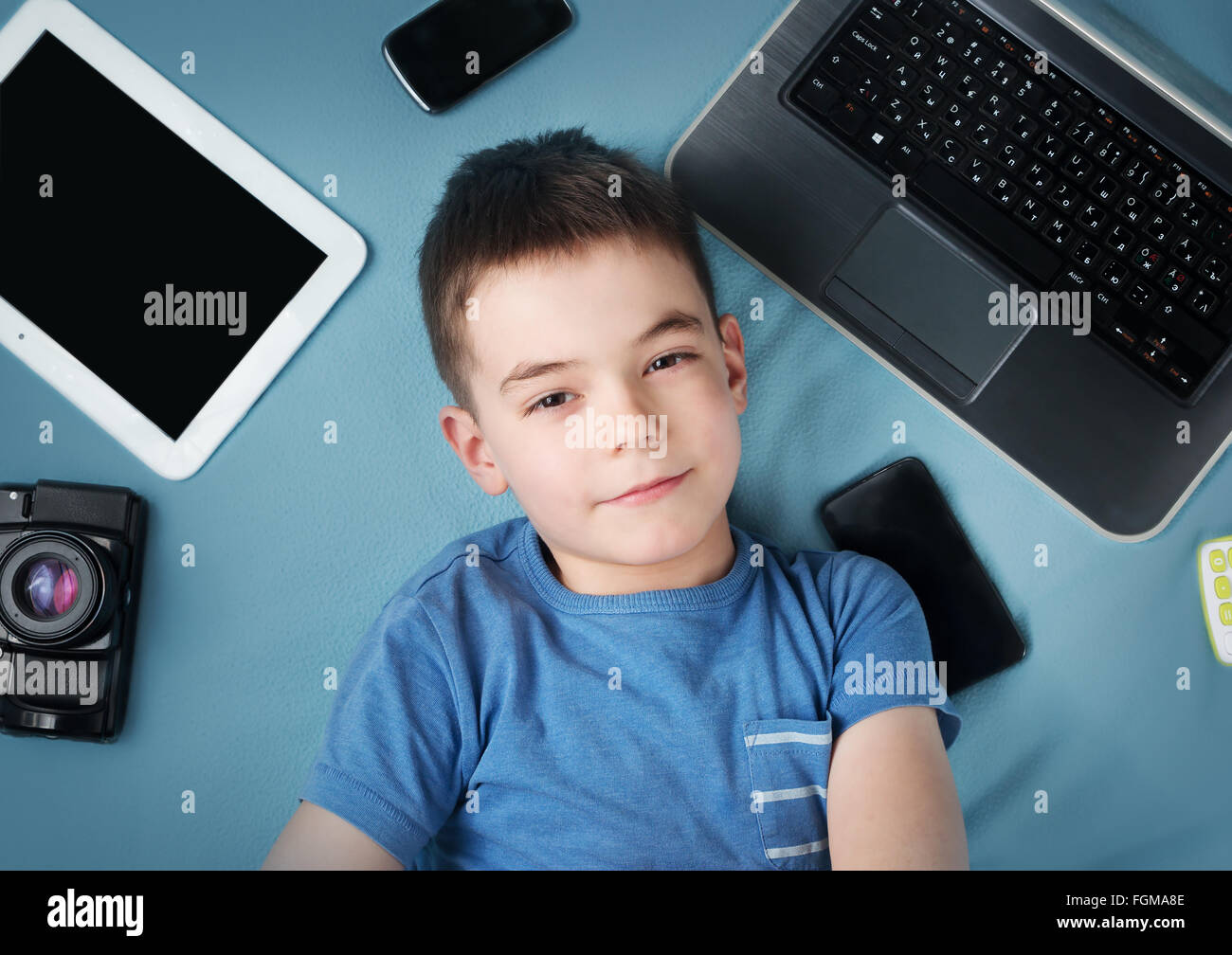 boy on blue blanket background with laptop - Stock Image