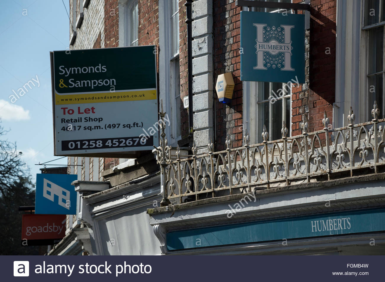 Numerous Estate and Letting Agent signs and boards above premises in Market Place, Blandford Forum, Dorset, England - Stock Image